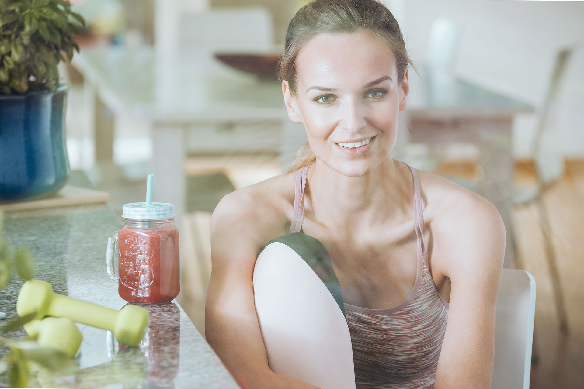 Smiling sportswoman drinking healthy cocktail