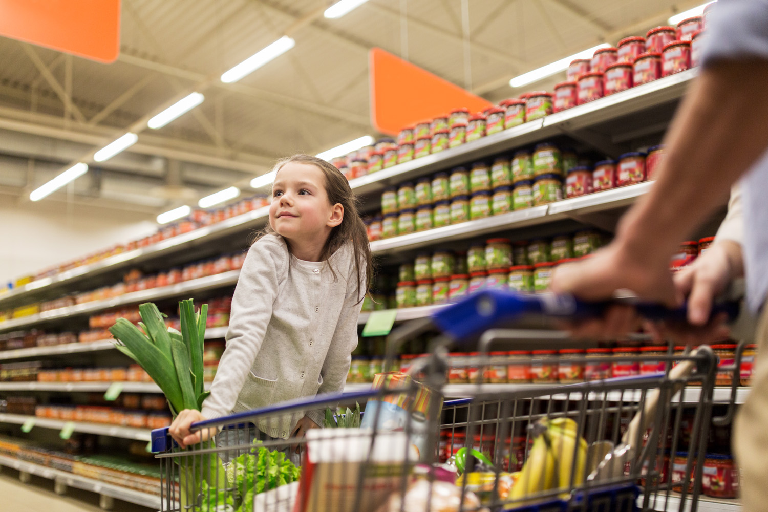 child with father buying food at grocery store