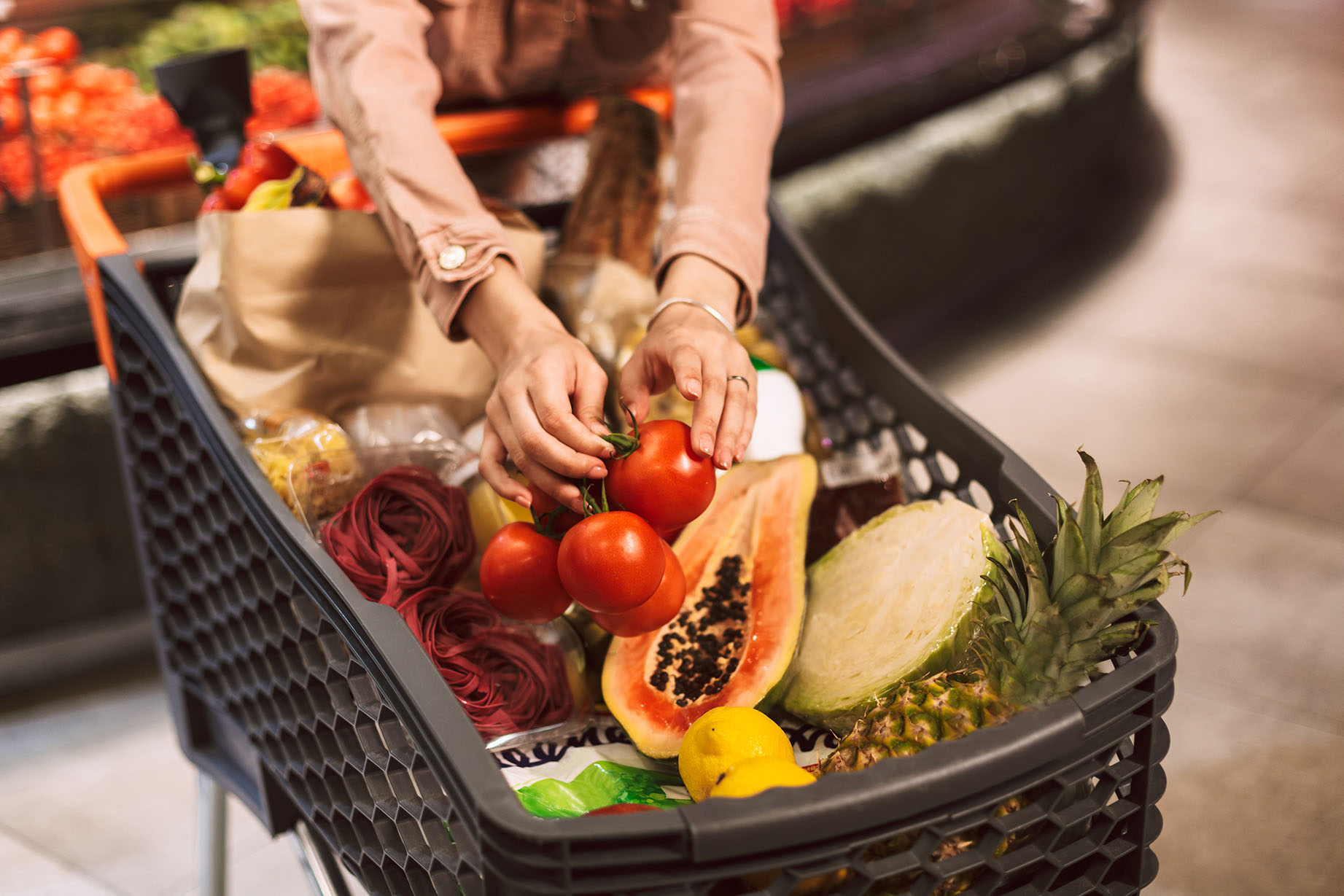 Close up woman hands holding tomatoes in trolley full of fresh