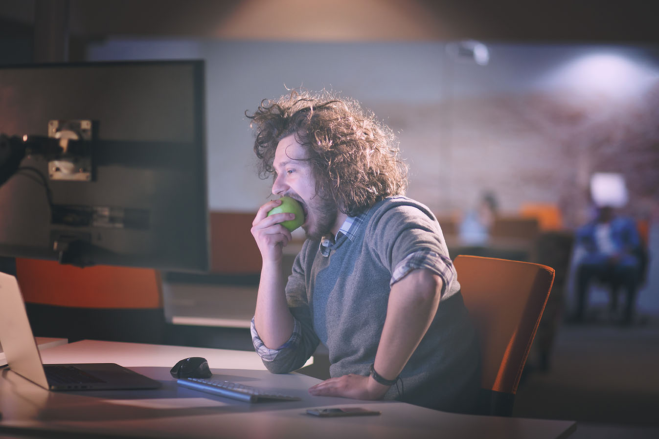 man eating apple in his office